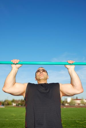 gripping bars: Strong man doing pull ups on a bar in a field with blue sky in the background.