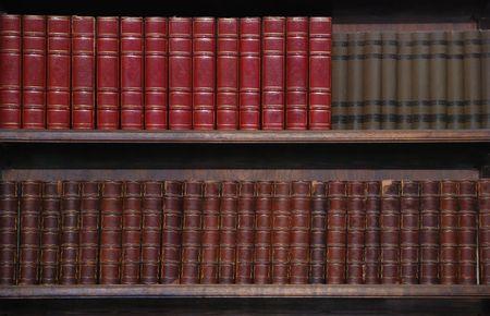 Twee rijen van oude boeken op boeken kasten.  Stockfoto