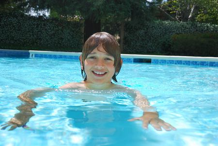 Smiling teen boy swimming in the pool surrounded with white flower bushes in the background. Stock Photo - 4987442