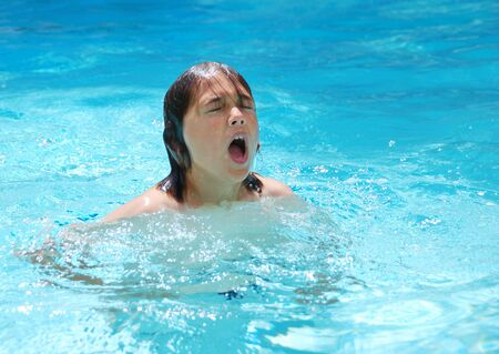 gasp: Teen boy just coming out of the water while swimming in the pool.