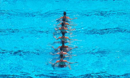 A seven women synchronized swimming team performing.