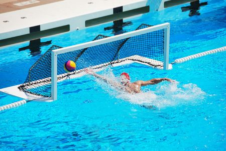 water power: A water polo goalkeeper misses the ball going into the net of the goal.