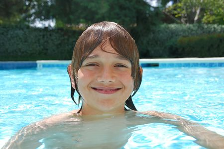 Smiling teenage boy swimming in the pool surrounded with white flower bushes in the background.