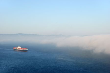 A tanker carrying containers flowing into the fog. photo