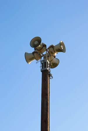 Four sirens on a pole with blue sky in the background. photo