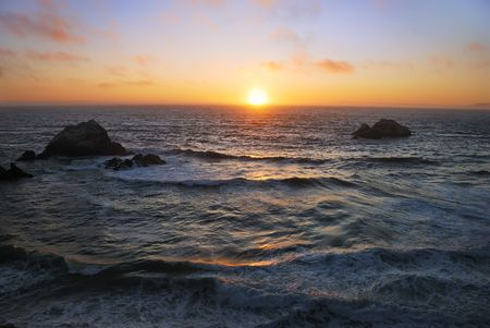 Sunset above the wavy Pacific as seen from the Ocean Beach in San Francisco, California. Stock Photo