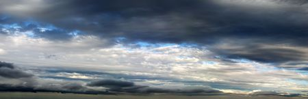 Panorama of white and dark clouds and patches of blue sky.