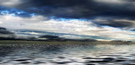 Panorama of white and dark clouds and patches of blue sky reflected in water.