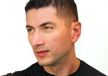 頭の黒い髪と青い目の白い背景の上に孤立した黒の t シャツを着てハンサムな白人男性のショット。