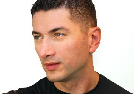black hair blue eyes: A head shot of a handsome Caucasian man with dark hair and blue eyes wearing black t-shirt isolated over white background. Stock Photo