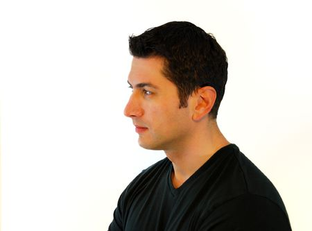 see side: A profile of a pensive man in black t-shirt over white background.