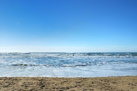 Ocean Beach in San Francisco California with waves coming to the sand and blue sky background.