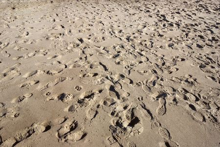 Shoe footprints in the sand in various directions. Stock Photo