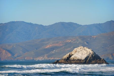 A view from Ocean Beach in San Francisco California with wavy ocean and Marin County and blue sky in the background