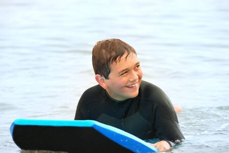 Smiling teenage surfer laying on his bodyboard in the ocean. Stock Photo