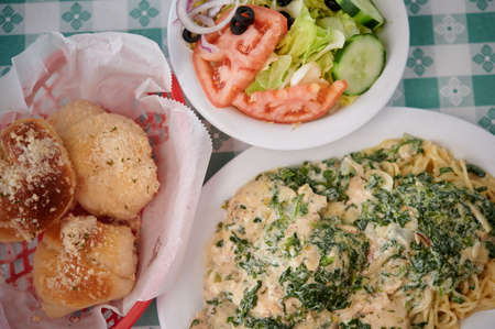 Close up on lemon chicken pasta with garlic rolls and Italian salad meal