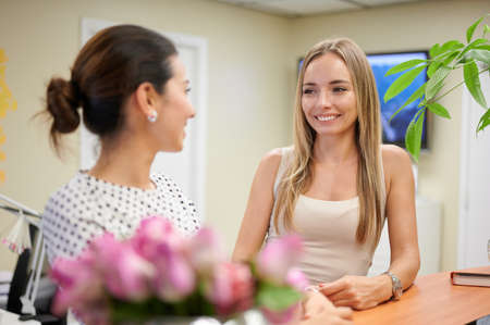 Two female looking at each other and smiling by receptionist desk professional services