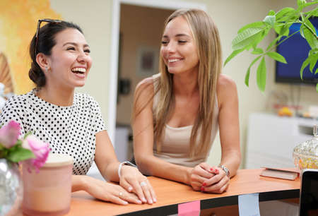 Two young ladies smiling by receptionist desk professional services office