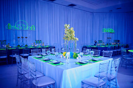 Beautiful orchid flower arrangement set up for a wedding party in a ballroom with lucite chairs and decoration