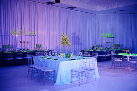 Fancy guest square table set up for a wedding or social event in the ballroom orchid and lucite chairs draped walls