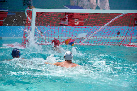 A water polo player scores a goal, goalkeeper misses the ball went into the net