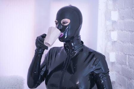 jolie personne de mode en caoutchouc latex en combinaison noire sur le rebord de la fenêtre blanche seule Banque d'images