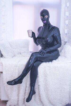 jolie personne de mode en caoutchouc latex en combinaison noire sur le rebord de la fenêtre blanche seule