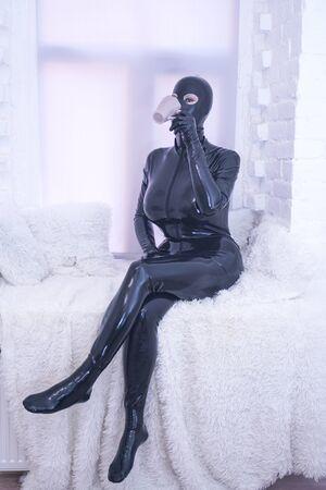pretty latex rubber fashion person in black catsuit on white windowsill alone Banque d'images