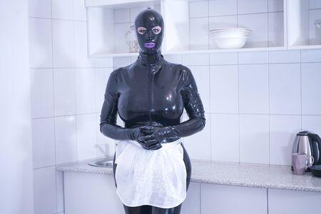 Linda mujer de talla grande en traje de mucama posando en la cocina blanca sola Foto de archivo