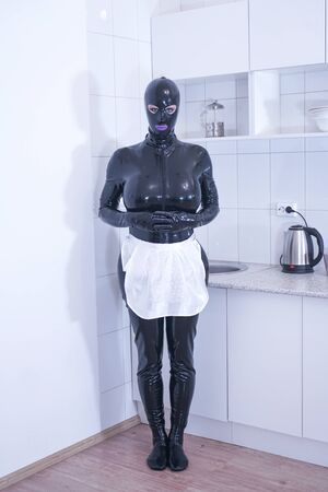 carina donna taglie forti in costume da cameriera in posa da sola sulla cucina bianca