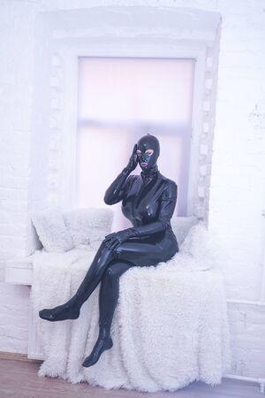 pretty latex rubber fashion person in black catsuit on white windowsill alone