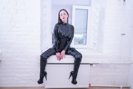 Schöne Frau in Glamour-Latexkleidung posiert im weißen Raum Standard-Bild