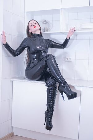 Beautiful woman in latex suit on white kitchen background