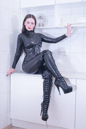 Schöne Frau im Latexanzug auf weißem Küchenhintergrund Standard-Bild