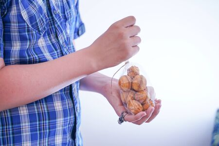 cute hungry teenager boy with fresh small bake sweets on white room background alone Zdjęcie Seryjne