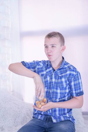 cute hungry teenager boy with fresh small bake sweets on white room background alone Stock Photo