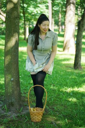 Asian girl resting in the summer in the Park in the intense heat in the bright sun alone