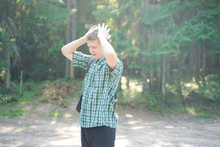 teenager boy lost alone in the countryside and scared in the forest