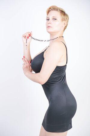 Portrait de jolie jeune femme potelée en robe noire moulante