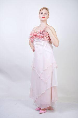 Porträt einer kurzhaarigen, prallen Frau im rosa Abendkleid