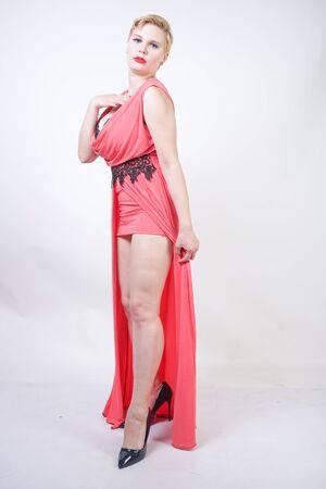 Porträt einer kurzhaarigen, prallen Frau im rosa Abendkleid Standard-Bild