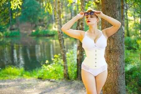 Sexy young woman in white lingerie with latex corset