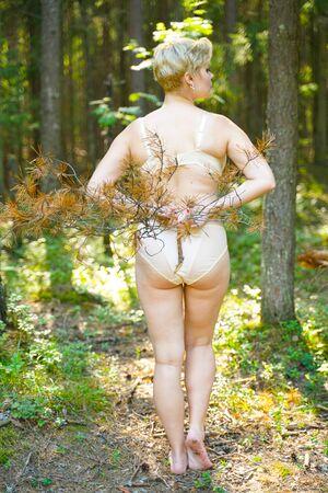 Chica en lencería beige camina en el verano en el parque