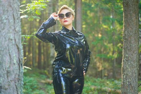 latex rubber fashion woman walking in the forest Banco de Imagens