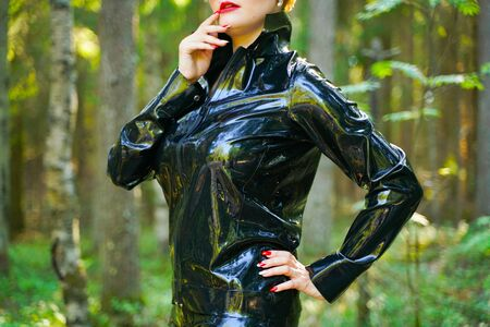 latex rubber fashion woman walking in the forest Imagens