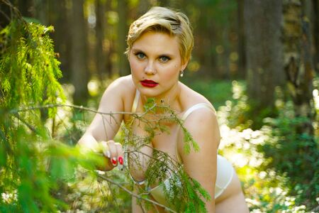 Girl in beige lingerie walks in the summer in the park