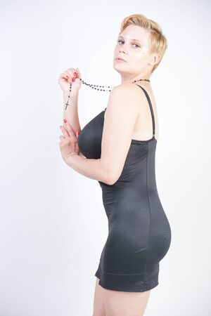 Portrait of attractive chubby young woman in tight black dress