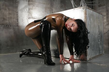 Beautiful woman in latex suit on a dark background with chains