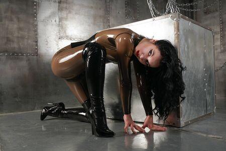 Bella donna in tuta di lattice su uno sfondo scuro con catene