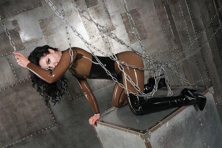 Schöne Frau im Latexanzug auf dunklem Hintergrund mit Ketten Standard-Bild